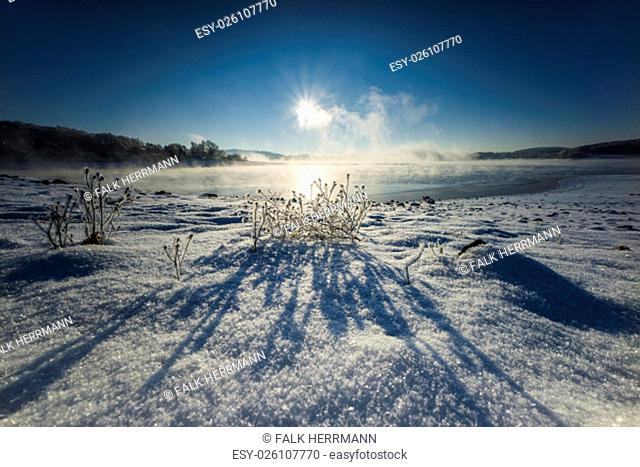 sunrise in the snow with fog and erupting solar am see
