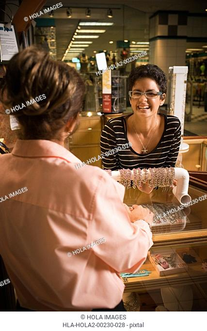Young woman helping customer in jewelry store