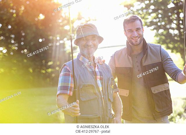 Portrait smiling father and adult son with fishing rods