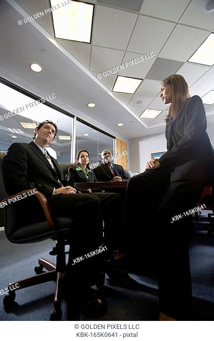 Low angle view of business men and women meeting in a formal conference room