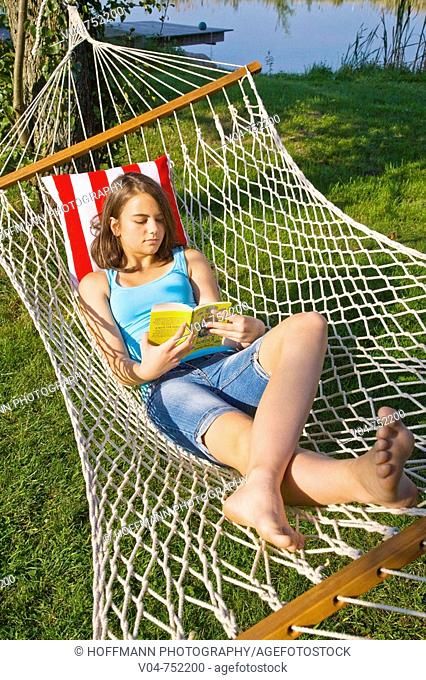 Teenaged girl reading a book in a hammock outdoors in a garden