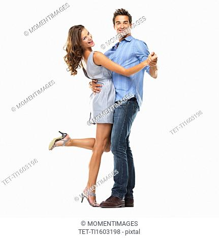 Studio shot of young couple dancing together and smiling