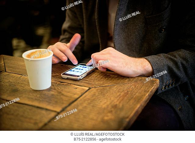 Closeup of hands of a man having coffee and manipulating a cell phone in a coffee shop in London, England, UK, Europe