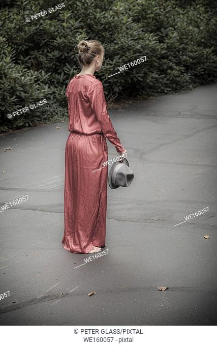 Young woman standing on her driveway, holding a hat