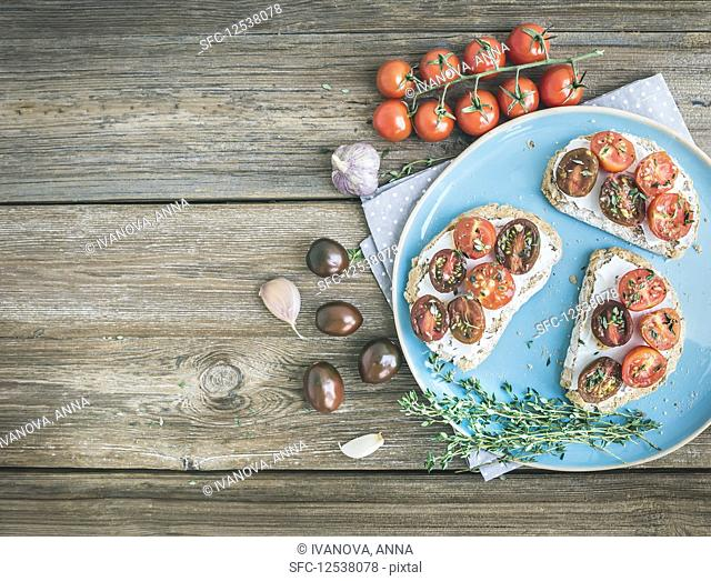 Rustic breakfast set of sandwiches with soft cream-cheese, cherry-tomatoes roasted with garlic and thyme