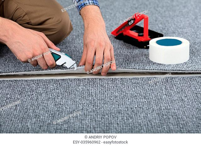 Close-up Of Carpenter Hand's Laying Carpet Using Cutter
