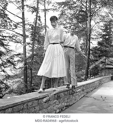 British actress Audrey Hepburn (Audrey Kathleen Ruston) and her husband and American actor Mel Ferrer walking on a low wall. Buergenstock, 1960