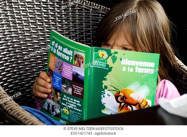 A little girl reads a book about farms called, 'Welcome to the Farm.'