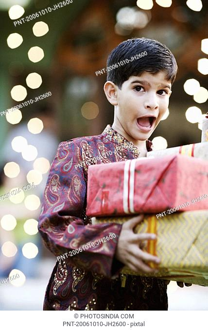 Close-up of a boy holding two gifts
