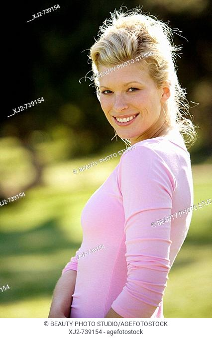 Woman standing outdoors looking at camera