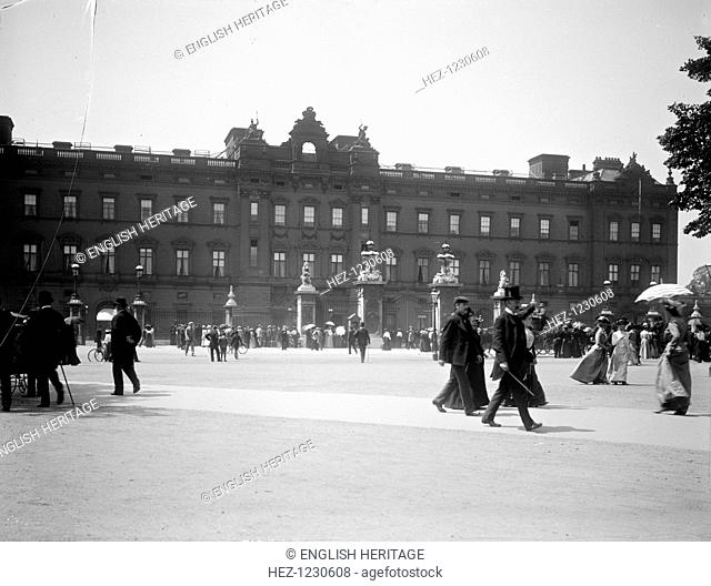 Sightseers crowd around the gates of Buckingham Palace, London. This view shows the public east facade as it looked after Edward Blore closed off the courtyard...
