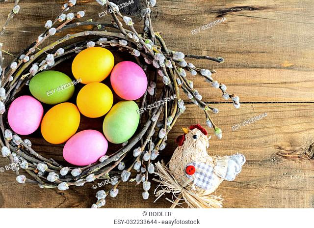 Easter background with copy space. Homemade hand painted colorful easter eggs in nest from willow branches and straw chicken for decoration close-up over retro...