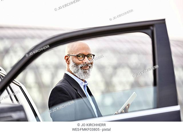 Businessman with digital tablet standing by car