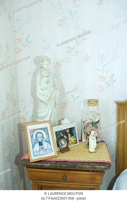 Night stand covered with religious objects and photos
