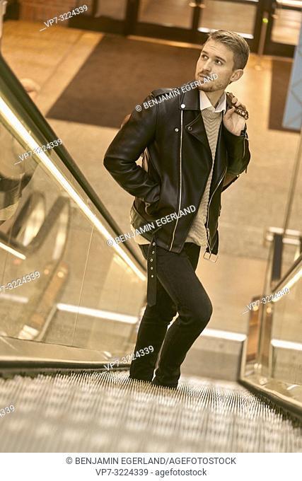 man standing on escalator, in Munich, Germany