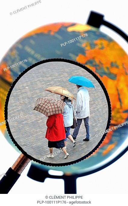 Tourists walking in the rain with umbrellas in summer seen through magnifying glass held against illuminated terrestrial globe