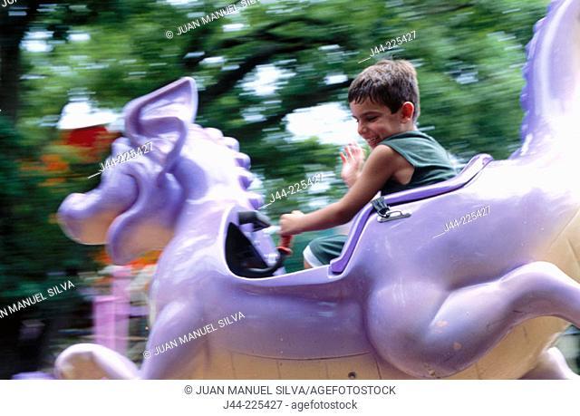 Boy riding a flying dragon in an amusement park