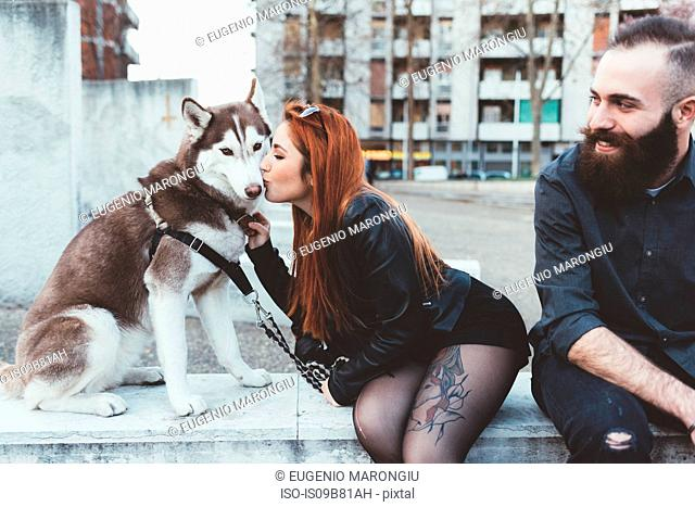 Red haired woman kissing dog