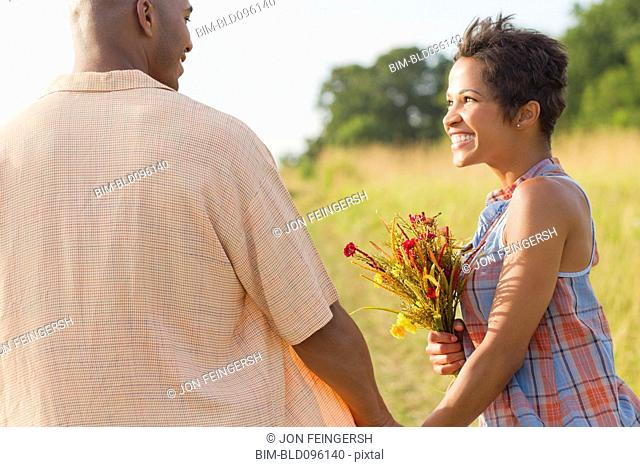 Woman with flowers holding hands with husband