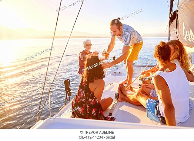 Friends relaxing, drinking champagne on sunny boat