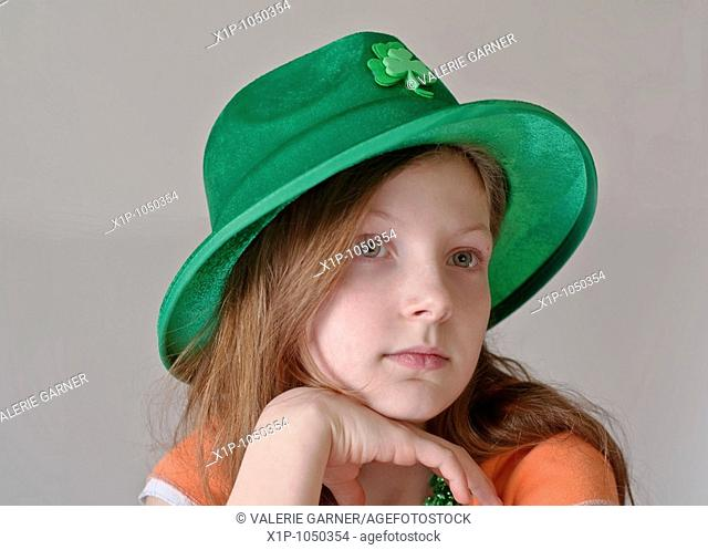 This beautiful green eyed, 9 year old Caucasian girl is wearing a green St Patrick's Day hat in a closeup on a light background Her facial expression is a more...