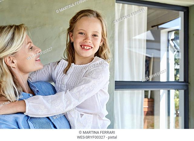 Portrait of happy little girl on mother's arms