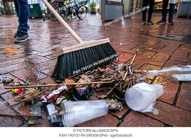 01 January 2019, Germany (German), Hannover: A man sweeps up burned fireworks and other remains of New Year's Eve on Lister Square