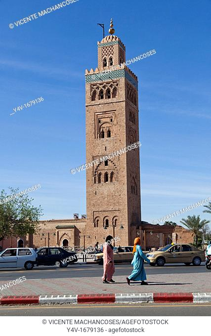 Two Arab women walking quietly down the sidewalk with the Koutoubia background