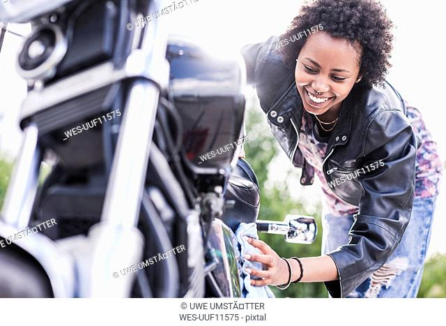 Young woman cleaning her motorcycle