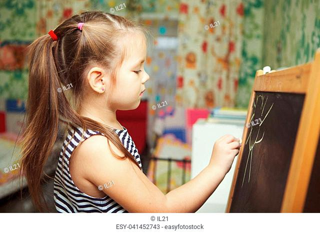 Girl with ponytail hairstyle in process of drawing picture of sun, kid creating new image with all carefulness on blackboard with chalk of green color