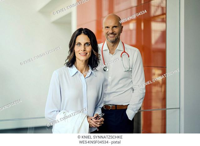 Friendly doctors standing in hospital, smiling