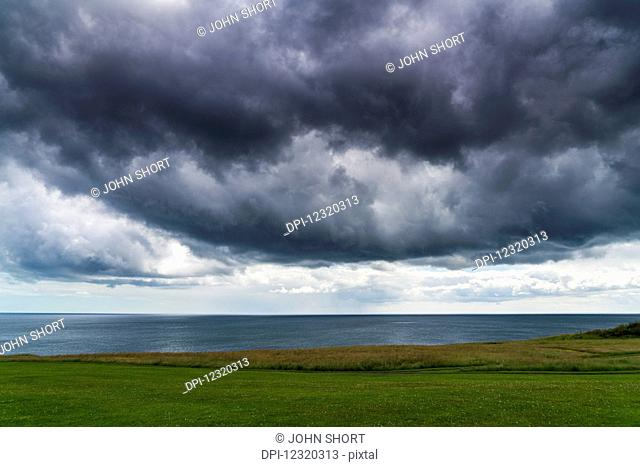 Dark clouds over the ocean and green fields along the coast; South Shields, Tyne and Wear, England