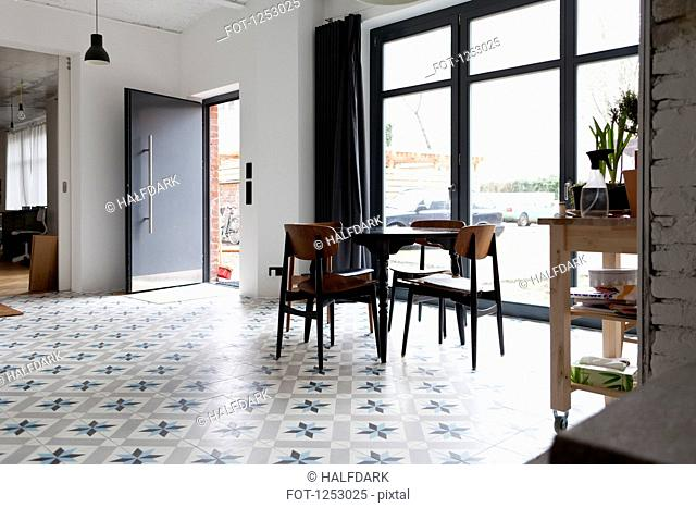 A hip tidy dining room with flooring that has a star shaped pattern