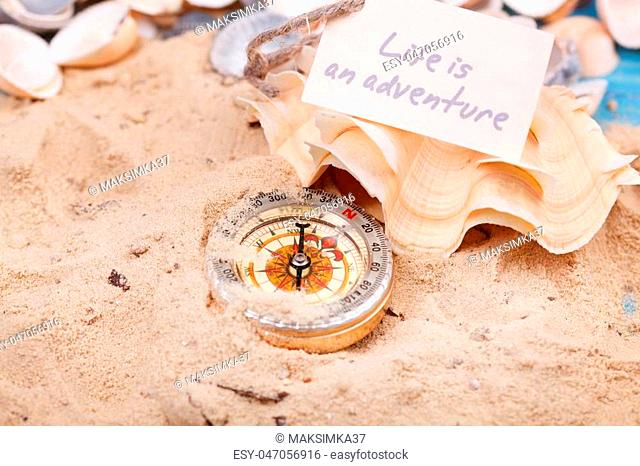 Compass in the sand with Message - Life is an adventure