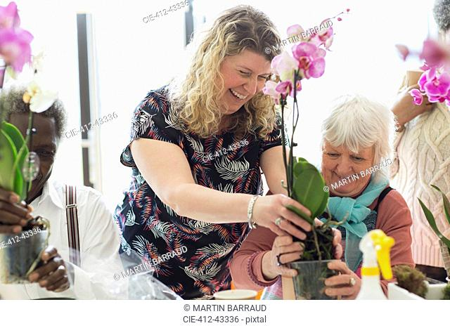 Smiling instructor and senior woman in flower arranging class
