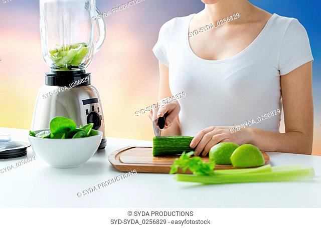 close up of woman with blender chopping vegetables