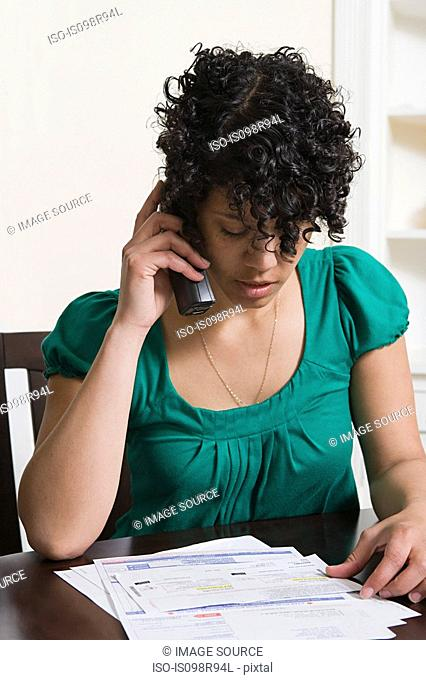 Woman on telephone looking at bills