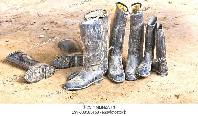 dirty plastic riding boots standing at the muddy gry ground