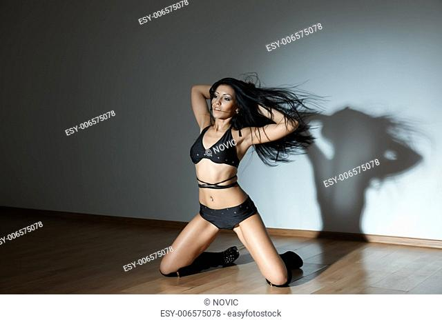 Woman in lingerie sitting in the dark ball room