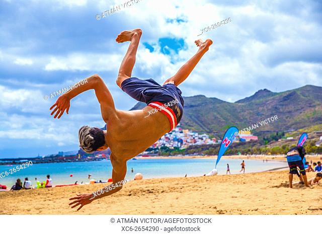 young male doing martial arts tricking sports on the beach