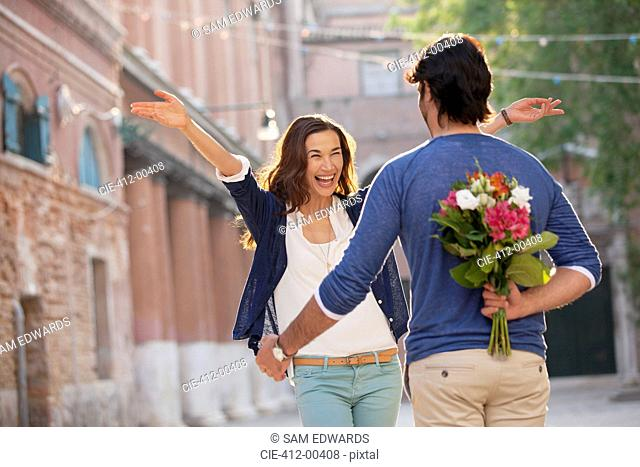 Enthusiastic woman approaching man with flowers behind back