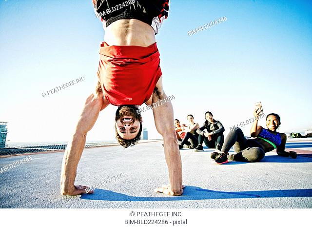 Woman photographing man doing handstand on urban rooftop