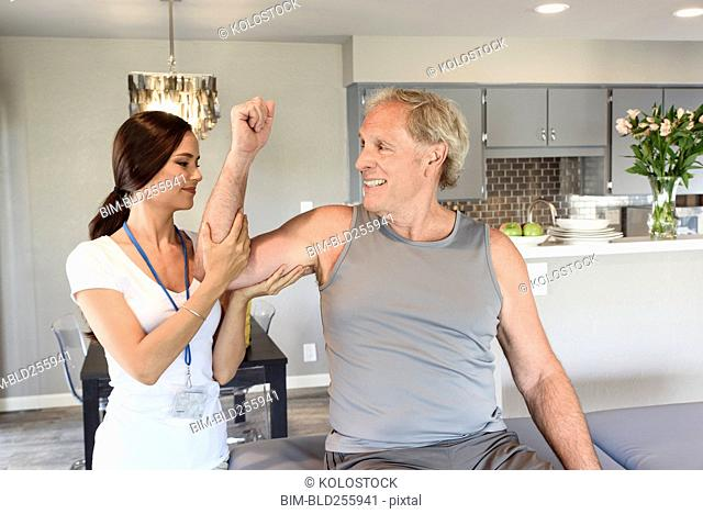 Physical therapist lifting arm of man