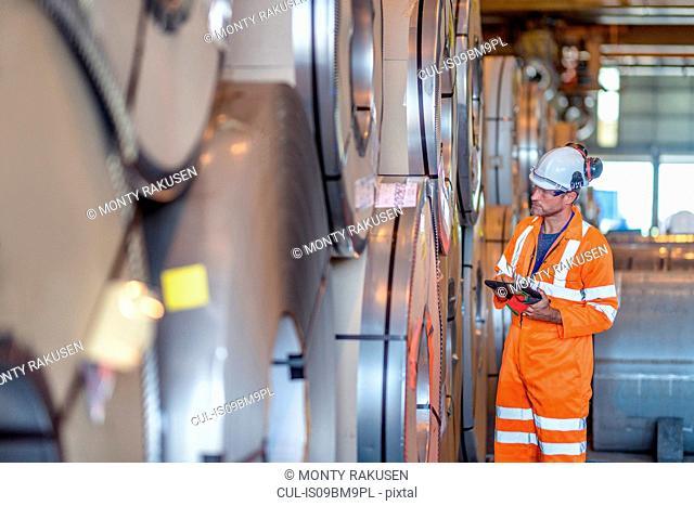 Worker using digital tablet by rows of sheet steel in storage at port