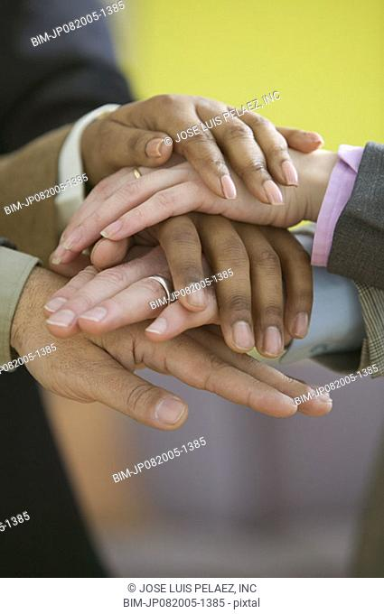 Close up of five hands stacked on top of each other