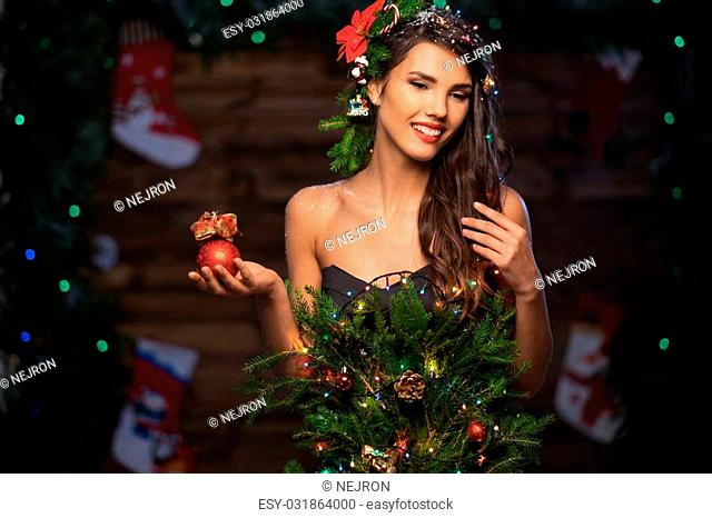 Woman in christmas tree dress in wooden interior holding christmas toy