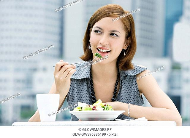 Close-up of a young woman eating salad