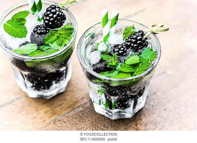 Two glasses of water with blackberries, ice cubes and mint