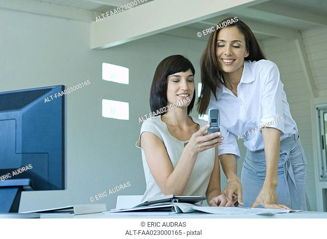 Two female co-workers, one showing the other cell phone
