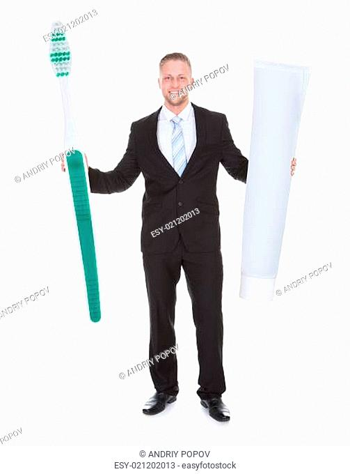 Smiling business man holding a large outsized toothbrush